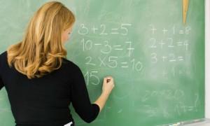 Elementary teacher writing arithmetic on blackboard, rear view
